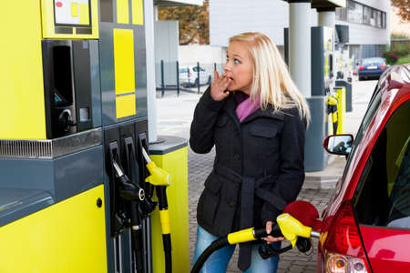 a young woman at a gas station gasoline tank  the cost of the car because of the gas prices are getting more expensive