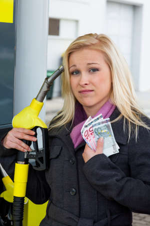 a young woman at a gas station gasoline tank  the cost of the car because of the gas prices are getting more expensive photo
