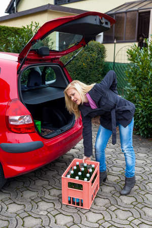 a young woman lifts a crate of bottles from their car  real life prevents back pain and herniated disc photo