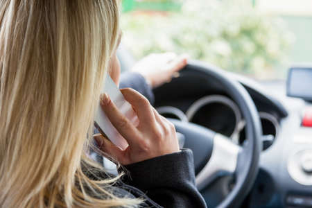 woman driving car: a young woman on the phone with their phone without handsfree in the car
