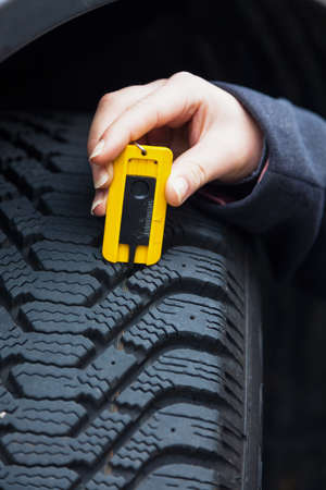 depth measurement: a young woman is measuring the tread depth of her car tire