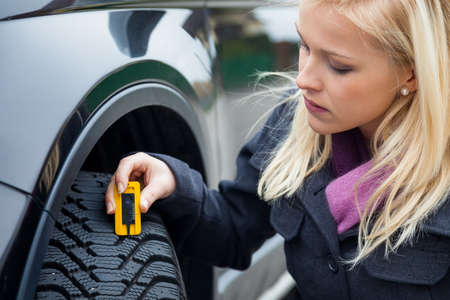 a young woman is measuring the tread depth of her car tire  the proper depth in the tread of a tire can prevent accidents  photo