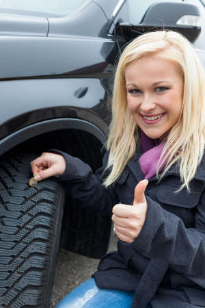 proper: a young woman is measuring the tread depth of her car tire  the proper depth in the tread of a tire can prevent accidents