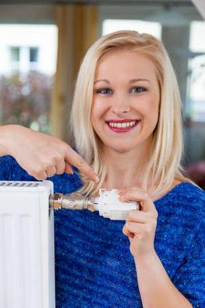 ordenanza: para el ahorro de energía y la reducción de potencia, una mujer joven, la temperatura en la sala de estar