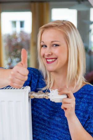 reducing: for saving energy and reducing power, a young woman, the temperature in the living room Stock Photo