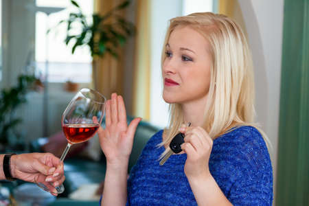 wine road: a young woman with car keys refused a glass of wine  do not drink and drive