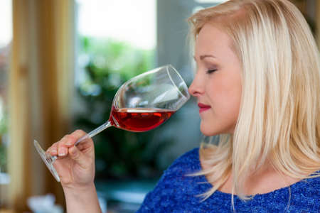 a young woman with a wine tasting  try a glass of red wine in the glass Stock Photo - 16469371