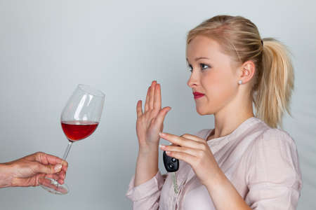 steadfast: a young woman with car keys refused a glass of wine  do not drink and drive