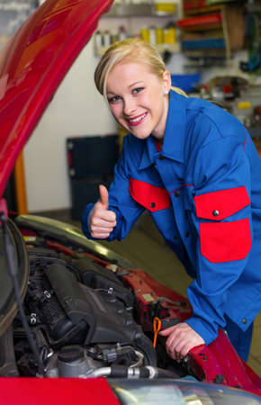 auto service: a young woman as a mechanic in a garage  rare professions for women  car is being repaired in the workshop
