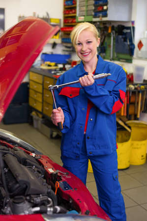 a young woman as a mechanic in a garage  rare professions for women  car is being repaired in the workshop Stock Photo - 16469372