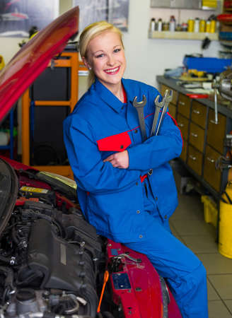 repaired: a young woman as a mechanic in a garage  rare professions for women  car is being repaired in the workshop