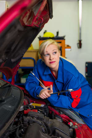 a young woman as a mechanic in a garage  rare professions for women  car is being repaired in the workshop Stock Photo - 16469370