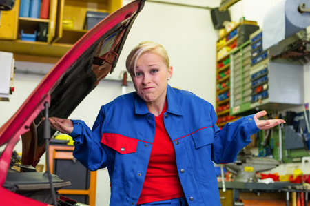 unsuspecting: a young woman as a mechanic in a garage  rare professions for women  car is being repaired in the workshop