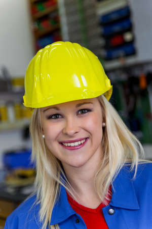 young mechanic with yellow helmet and wrench in a workshop  rare female occupations Stock Photo - 16469374