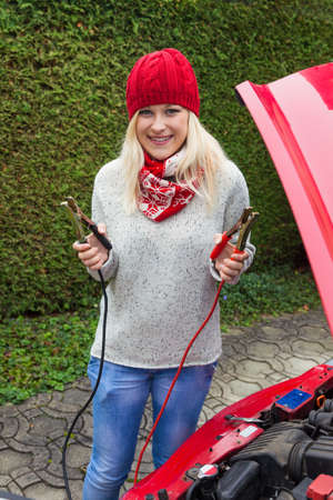bridging: a young woman starts her car with jumper cables  jump start on cold days in winter Stock Photo
