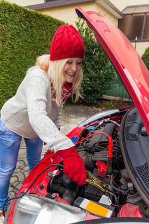 starter: a young woman starts her car with jumper cables  jump start on cold days in winter Stock Photo