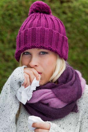 estornudo: una mujer joven tiene un resfriado y tiene un fr�o del oto�o es el momento para la gripe, los resfriados y la gripe