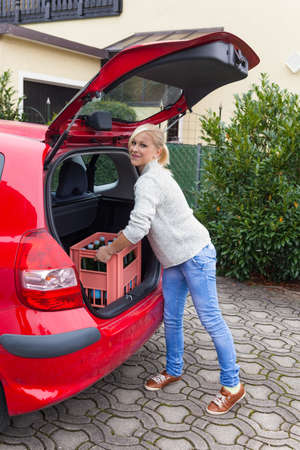 car trunk: a young woman lifts a crate of bottles from their car  real life prevents back pain and herniated disc