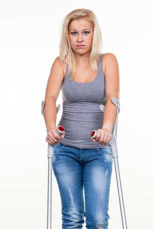 pierna rota: una mujer joven con muletas foto simbólica de los accidentes, los accidentes domésticos y de seguros