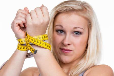 desorden: una mujer joven con una cinta de medir antes de la siguiente dieta eliminación rápida y