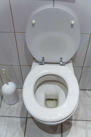 a toilet in an apartment  with an open toilet seat