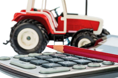 peasantry: a tractor and a red pen on a calculator  costs of fuel, insurance and wear  costs and subsidies in agriculture