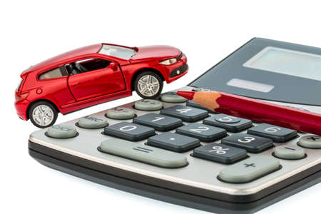a car and a red pen on a calculator  costs of fuel, insurance and wear  car costs are not paid by commuters Stock Photo - 16678877