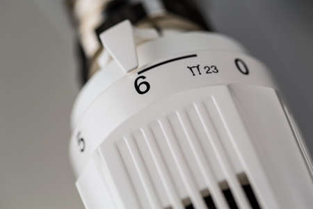 the thermostat of a radiator is turned up  high room temperature result in high energy costs photo