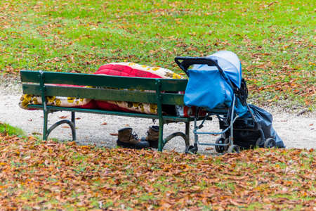 tristesse: on a park bench has a homeless man resigned to sleep Stock Photo