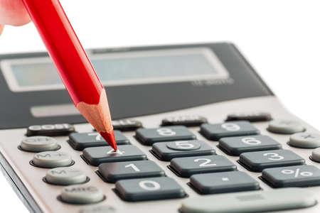een rode pen op een rekenmachine besparen op kosten, uitgaven en het budget voor slechte economie Stockfoto