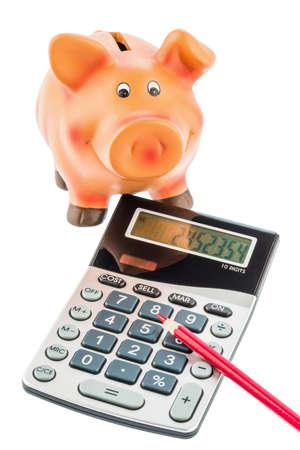 budget crisis: a red pen on a calculator beside a piggy bank  save on costs, expenditures and budget  interest rates for savers