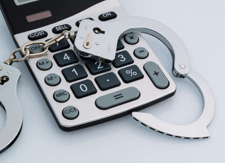remand: calculators and handcuffs on a white background  representative photo of white-collar crime
