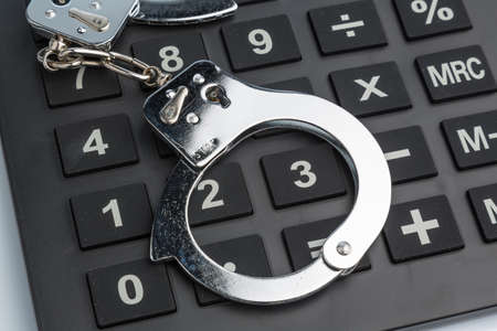 calculators and handcuffs on a white background  representative photo of white-collar crime Stock Photo - 16872218