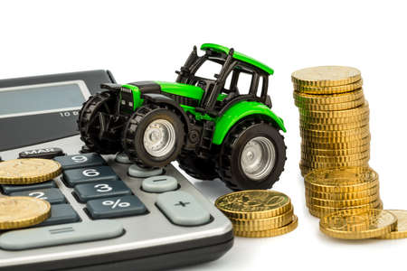 farmers in agriculture have to reckon with rising costs  higher prices for food, fertilizer and plants  tractor with coins and calculator Stock Photo - 17122214