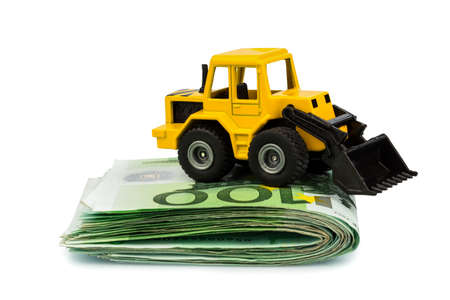 an excavator stands on euro banknotes  symbol photo for costs, revenues and grants in the construction industry and the construction industry Stock Photo - 17122020