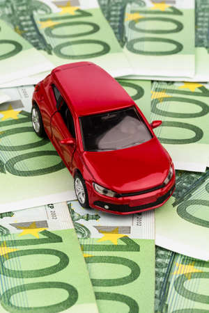 auto leasing: a car stands on euro banknotes  cost of purchasing a car, petrol, insurance and other car costs