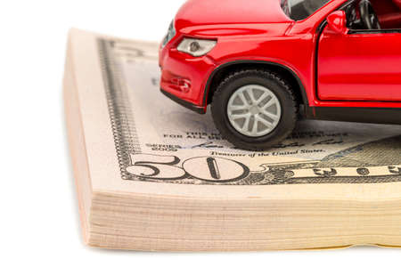 a car stands on dollar bills  cost of purchasing a car, petrol, insurance and other car costs Stock Photo - 17122336
