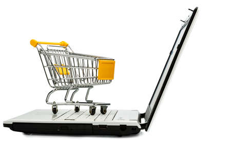 consumerist: cart standing on the keyboard of a laptop, symbol photo for online shopping and consumer behavior