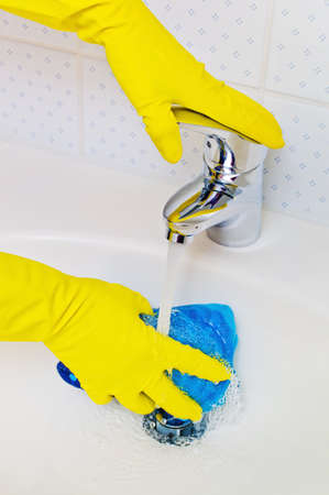 putz: the sink of a bathroom is cleaned with latex gloves