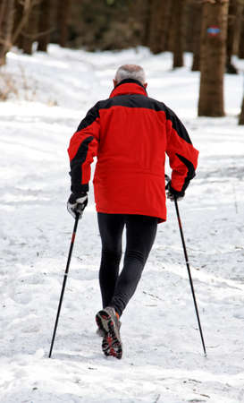 senior walking in winter on snow in nordic photo