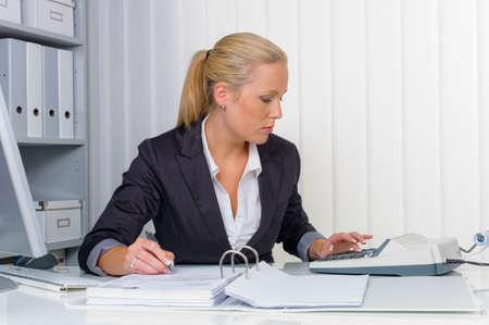 een accountant aan het werk in het kantoor met rekenmachine Stockfoto