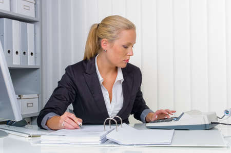 auditor�a: un contador en el trabajo en la oficina con la calculadora