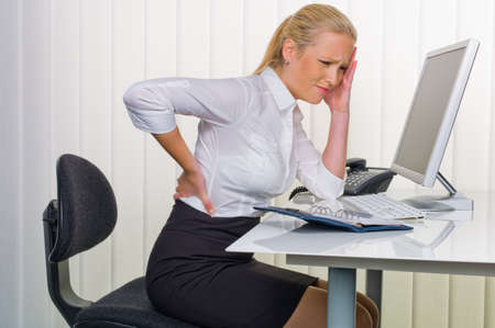 suffer: a woman with back pain from sitting so long in the office  health and welfare at work