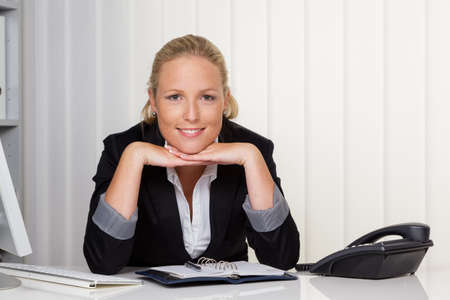owning: a young successful woman sitting at her desk in the office  Stock Photo
