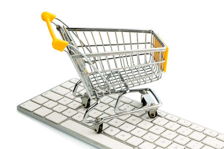 consume: cart standing on the keyboard of a pc, symbolic photo for online shopping and consumer behavior