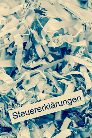 tax aligned: shredded paper tagged with tax returns, symbolic photo for tax burden and retention requirements