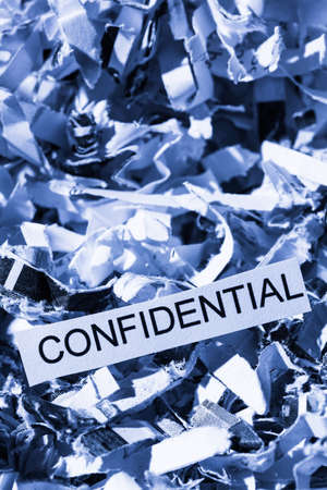 confidentiality: shredded paper tagged confidential, symbol photo for data destruction, bank secrecy and confidentiality Stock Photo