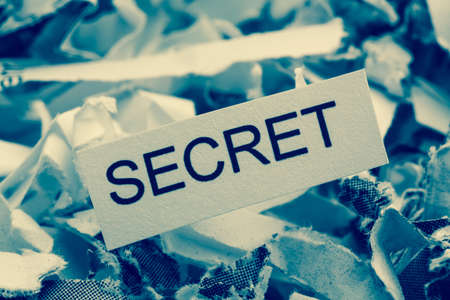 insider information: shredded paper tagged secret, symbolic photo for data destruction, banking secrecy and industrial espionage