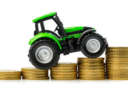 farmers in agriculture have to reckon with rising costs  higher prices for food, fertilizer and plants  tractor with coins Stock Photo - 17633907