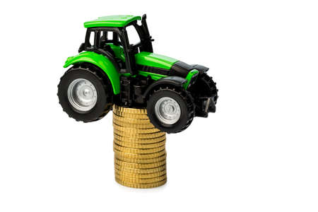 farmers in agriculture have to reckon with rising costs  higher prices for food, fertilizer and plants  tractor with coins Stock Photo - 17633661